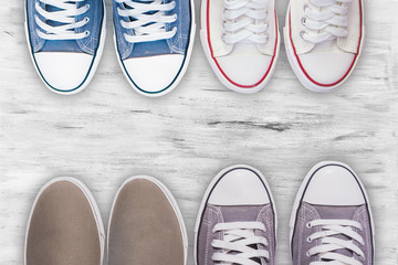 Top view Gray sneakers and blue sneakers and white sneakers other shoes on white wooden floor background, Wall mural