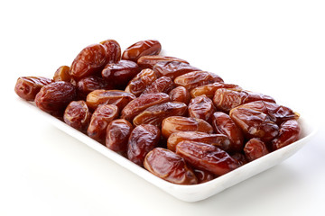 Fresh dates on a white plate against a white background