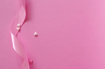 Schleifenband mit Zuckerherzen auf rosa Untergrund