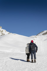 Couple admires the snowy landscape of Italian alps