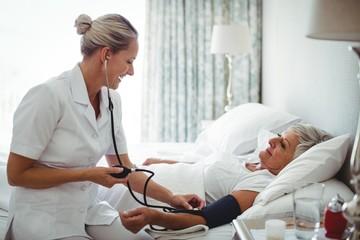 Nurse checking blood pressure of senior woman