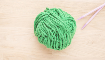 Ball of yarn and knitting needles on wooden table. The needlework thread is green. Concept of traditional hobby and a creative leisure activity.