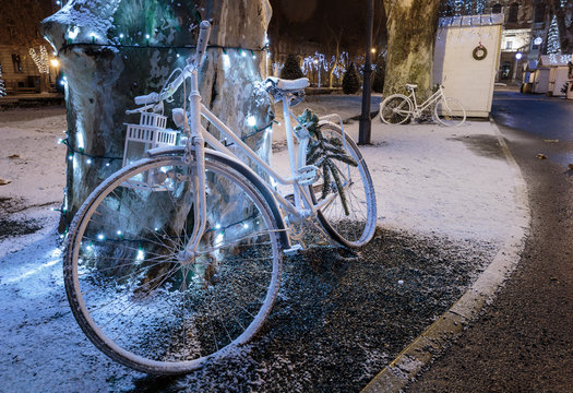 Advent in Zagreb, Christmas stall, tree decorated with lights and old white bicycle in foreground leaning on the tree in Zrinjevac park