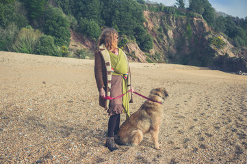 Woman with baby walking dog on beach