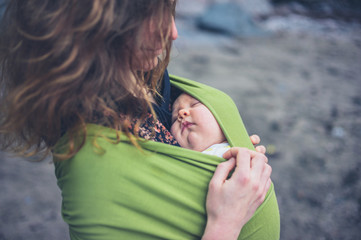 Young woman with baby in sling on beach