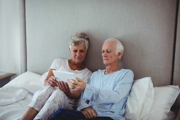 Senior couple using digital tablet on bed