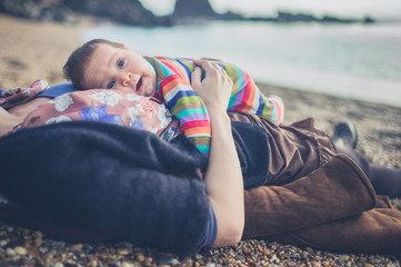 Mother relaxing on beach with baby