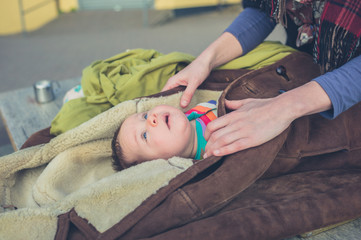 Mother wrapping baby in coat outside