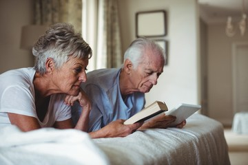 Senior woman reading and senior man looking at digital tablet