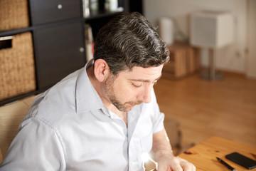 Man looking serious reading at table