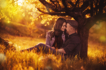 Love couple sitting under a tree in the colorful spring garden