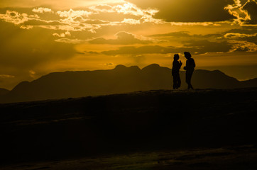 Silhouettes of two people walking on White Sand Dunes during sun