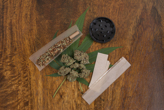 Cannabis sativa weed leaf and flower buds on wooden background with grindr and large smoking papers, copy space