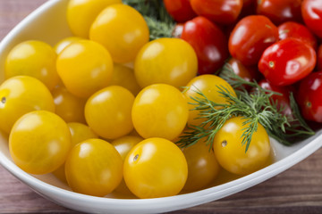 Bunch of red and yellow cherry tomatoes in a bowl