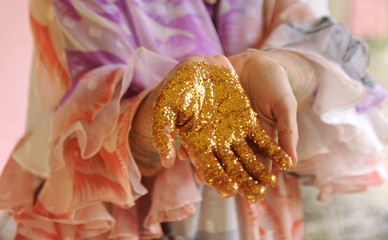 Woman's hand covered in gold glitter