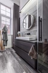 Wooden bathroom with round mirror
