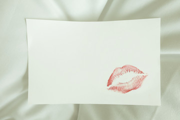 sexy red lipstick kiss on blank white note on white bed pillow sheet in the morning on valentine's day.