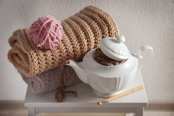 Plaids, yarn and teapot on white little table