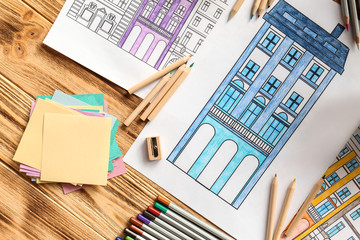 Composition of colouring pictures and pencils on wooden table