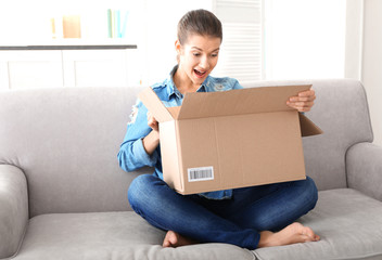 Beautiful young woman opening box with parcel while sitting on sofa at home