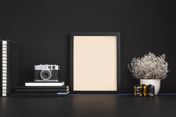 Black photo frame and camera on black desk.
