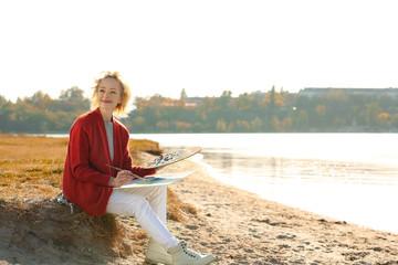 Senior female artist painting picture near river