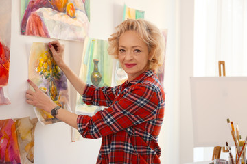 Senior female artist hanging picture in studio
