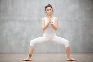 Portrait of beautiful young woman wearing white sportswear working out against grey wall, doing yoga or pilates exercise. Standing in Sumo Squat, Goddess pose. Full length