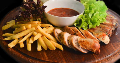 Meat sausages and fries on a wooden Board