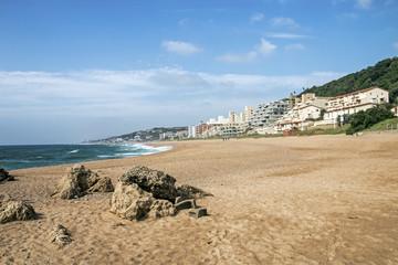 Rocks on Empty Sandy Beach Against Blue Skyline