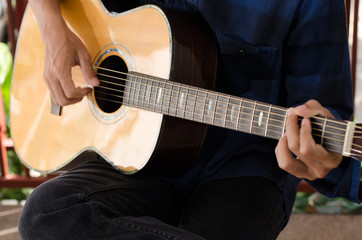 A young man playing acoustic guitar happy and relaxed in the day