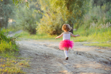 Little curly girl in a bright pink skirt tutu runs on a forest road, the view from the back.