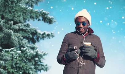 Winter young smiling african man enjoying listening music on sma