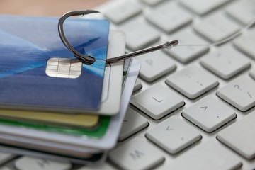 Bunch of credit cards in fishing hook on laptop