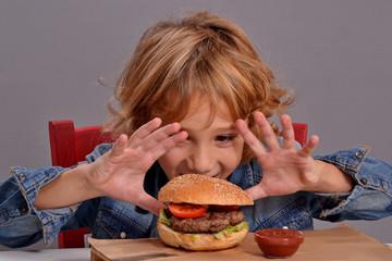 niño contento comiendo hamburguesa y patatas fritas.