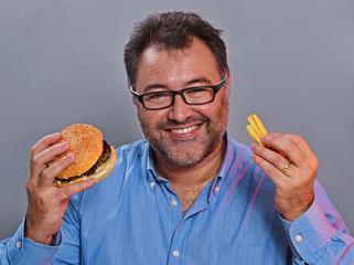 Disfrutando comiendo hamburguesa y patatas fritas.