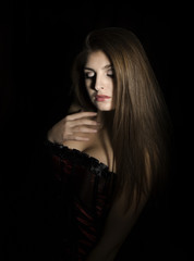 Portrait of a sensual young sexy woman wearing corset, touching her hair on black background