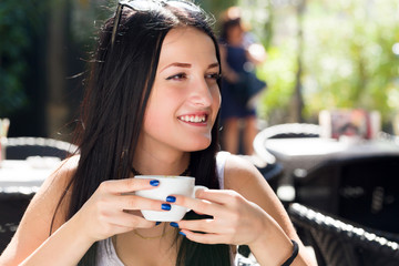 Portrait of young beautiful woman sitting in a cafe outdoor drin