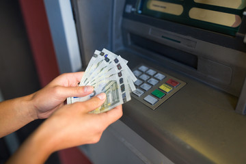 close up of hand withdrawing money at atm machine