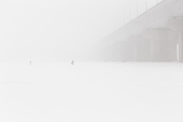 Bridge pillars and fishermans silhouettes on winter snowy river as small detail. Kiev. Ukraine. Minimalist landscape.