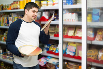 man buying Italian pizza in cooled food section