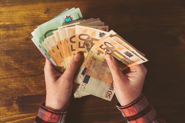 Female hands counting large amount of euro currency cash banknot