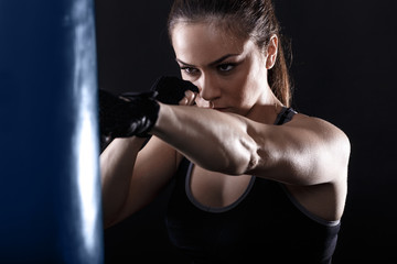 Studio shot of female boxer punching a boxing bag.