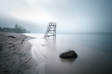 Lifeguard tower on the late autumn beach. Big stone in the water on foreground. Long exposure shot.