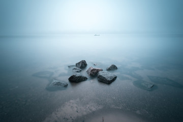 Coastal landscape of foggy river with fisherman in the boat as small detail. Stones in the water on foreground. Long exposure shot.