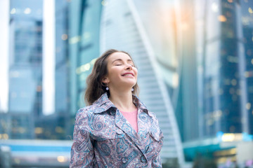 Portrait of young happy girl at street, her eyes closed with enjoyment, breathing at full outside. Lady feeling free, successful, ready to start day, visiting new town, blurred skyscraper background Wall mural