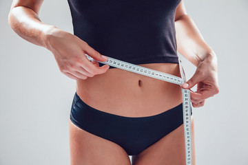 Athletic slim woman measuring her waist by measure tape on white background