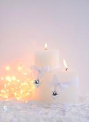 Christmas candles on the snow and Christmas lights. Festive Christmas background