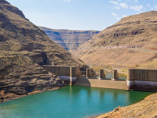 Downriver view of gorge and breakers at impressive Katse Dam hydroelectric power plant in Lesotho, Africa