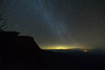 The milky way illuminated above the dark silhouette of the mountain.